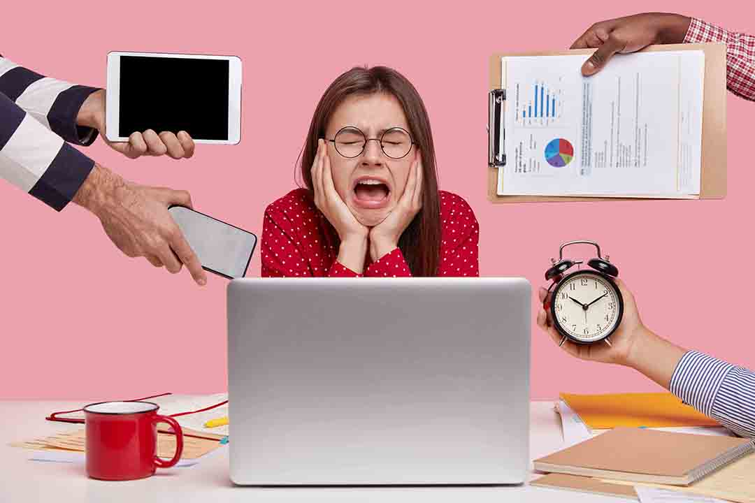 Melancholy, working concept. Depressed sad woman cries in despair, keeps mouh opened, wears round spectacles, has much work, prepares for exam, works on laptop computer, isolated on pink wall
