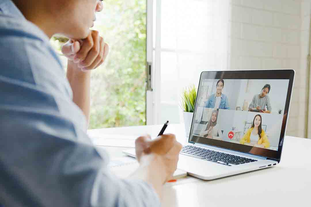 Young Asia businessman using laptop talk to colleagues about plan in video call meeting while work from home at living room. Self-isolation, social distancing, quarantine for corona virus prevention.